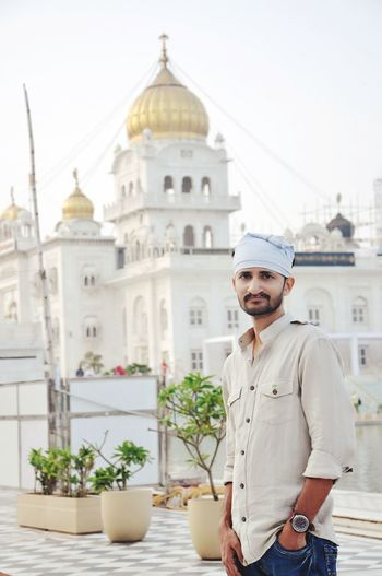 Portrait of man standing against golden temple
