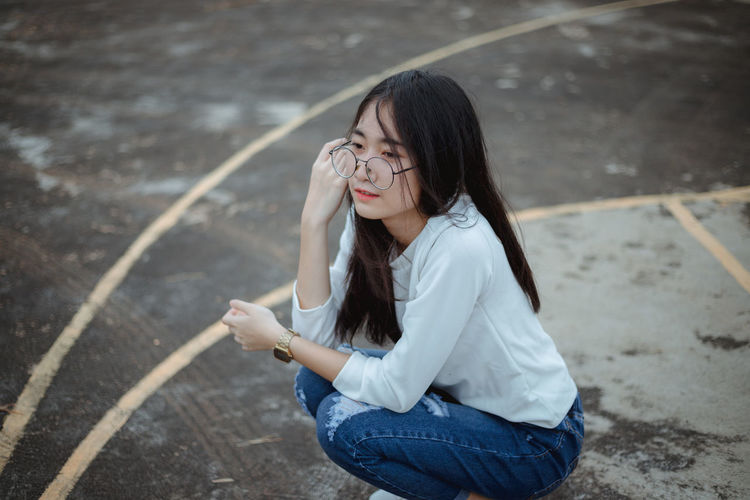 cute girl Adult Beautiful Woman Casual Clothing Day Emotion Girls Hair Hairstyle Holding Jeans Leisure Activity Long Hair One Person Outdoors Real People Sadness Sitting Teenager Three Quarter Length Women Young Adult Young Women