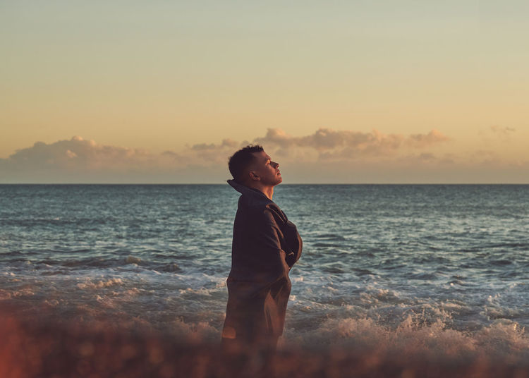 Young man standing at beach during sunset