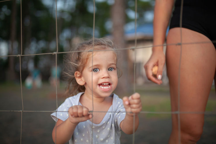 little caucasian girl standing behind the metal grid fence Child Childhood Females Family Emotion Women Girls Real People Togetherness Parent Innocence Family With One Child Mother People Happiness Portrait Smiling Daughter Grid Behind Fence Little Girl Woman Evening Summer Day Mother With Child Positive Emotion Happy People Laugh Children Close-up Hand Arm Hostage Freedom Concept Conceptual