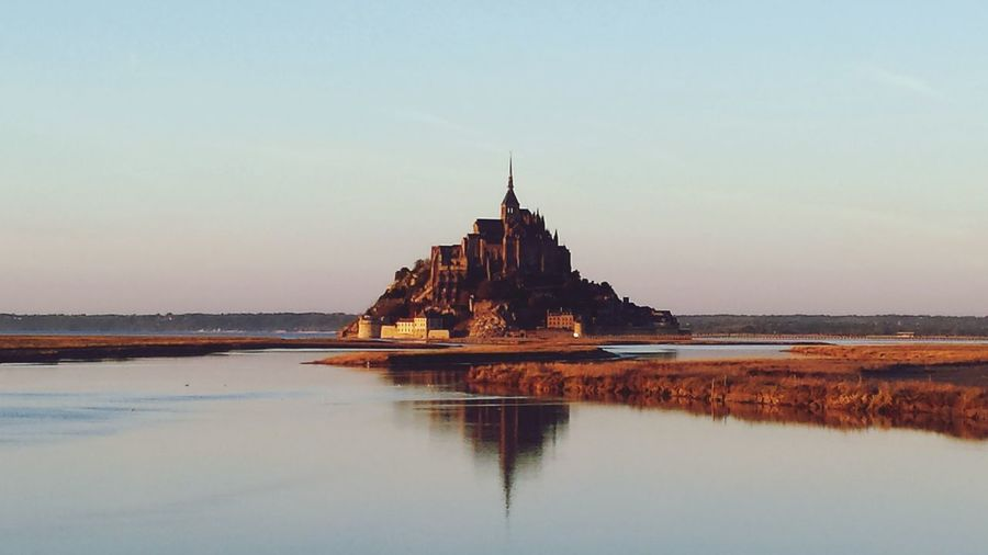 Reflection Of Mont Saint-Michel In River Against Clear Sky At Dusk