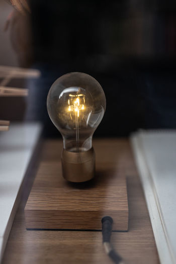 High angle view of illuminated light bulb on table