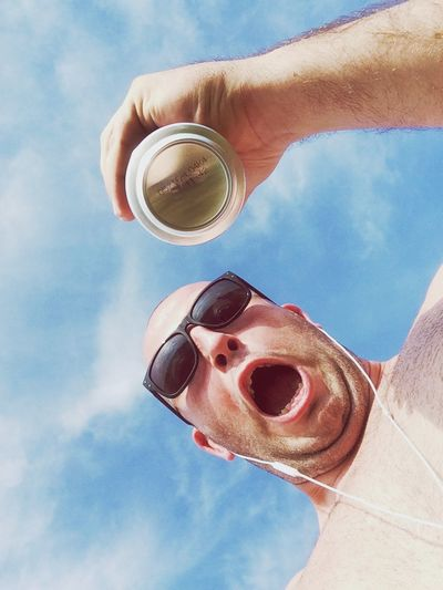 Low angle view of shocked shirtless man holding drink can against sky