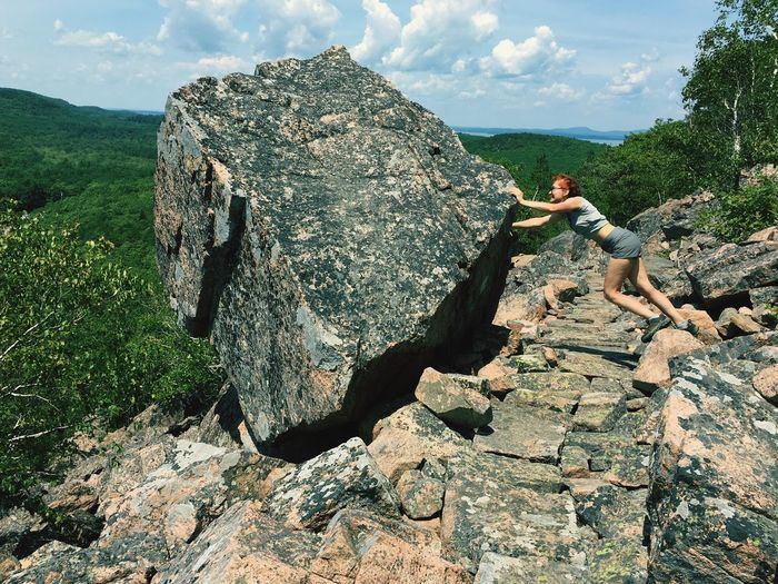 Mature woman pushing rock against sky during sunny day