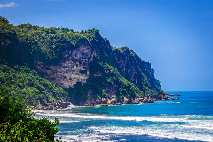 Parangtritis Beach, Yogyakarta, Indonesia Sea Water Beauty In Nature Scenics - Nature Land Beach Blue Tranquil Scene Nature Sky Tranquility Clear Sky Day Mountain Rock Tree Outdoors Horizon Over Water Beautiful Beach Parangtritis Yogyakarta INDONESIA