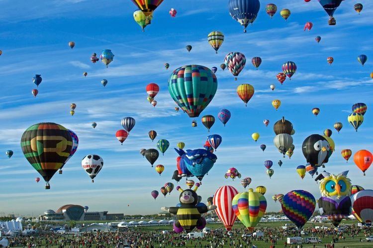 Hot Air Balloons Flying Over Field Against Sky During Festival