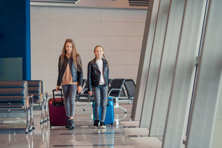 Full length of sisters with luggage walking at airport