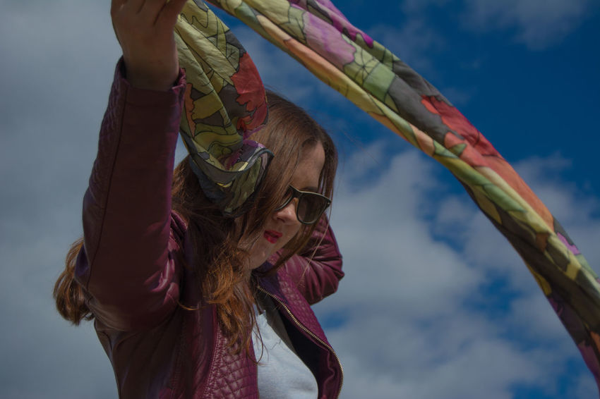 Portrait Of A Woman Adult Beauty Blue Clothing Cloud - Sky Females Focus On Foreground Girl Portrait Holding Leisure Activity Lifestyles Low Angle View Nature Outdoors Portrait Positive Emotion Real People Scarf Sky Springtime Sunglasses Wind Wind Motion Women