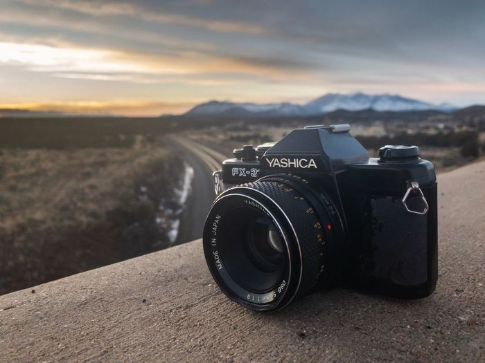 Close-up of camera against landscape during sunset