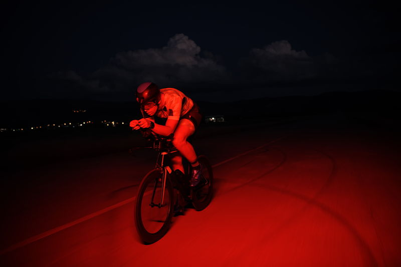 Full length of man riding bicycle on road at night