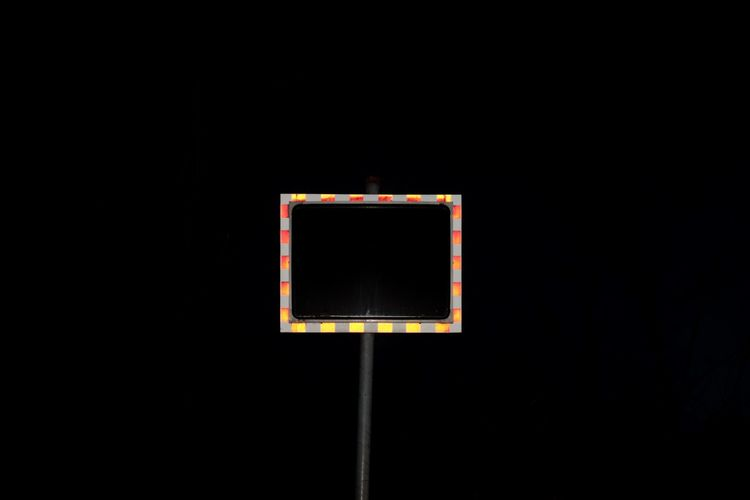 Close-up of basketball hoop against black background