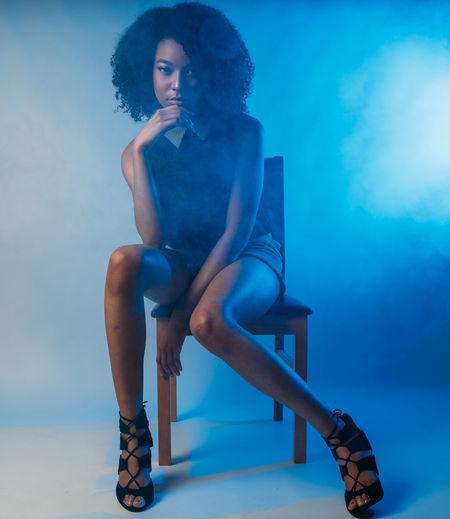 Full Length Portrait Of Confident Fashion Model Sitting On Chair In Illuminated Studio