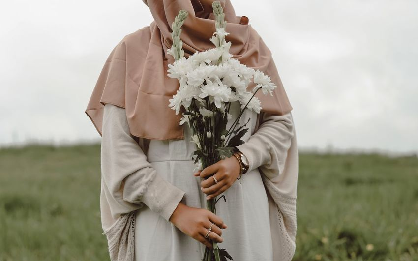 Midsection of woman holding flowers while standing on field
