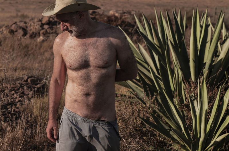 Shirtless man with cowboy hat standing by succulent plants on field