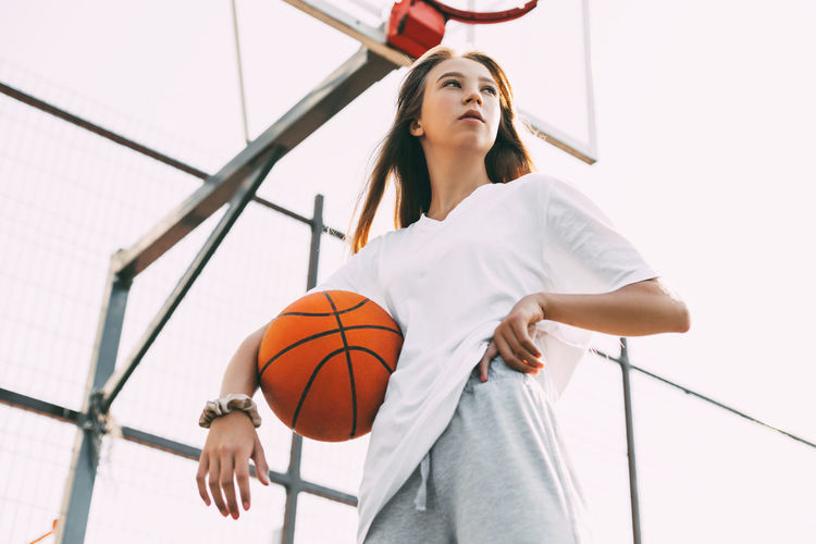 Portrait of young female basketball player. beautiful teen girl playing basketball.
