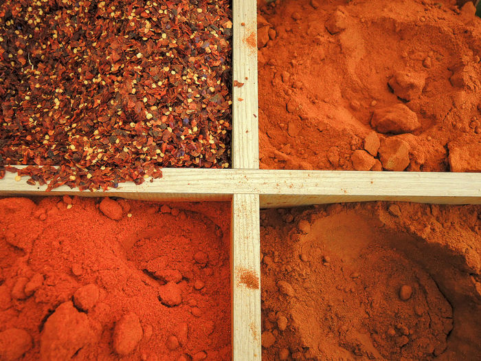 Directly above shot of red chili powders in containers at market stall