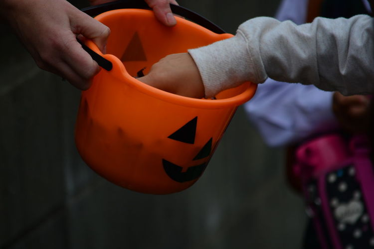 Cropped image of hands picking candy from halloween basket
