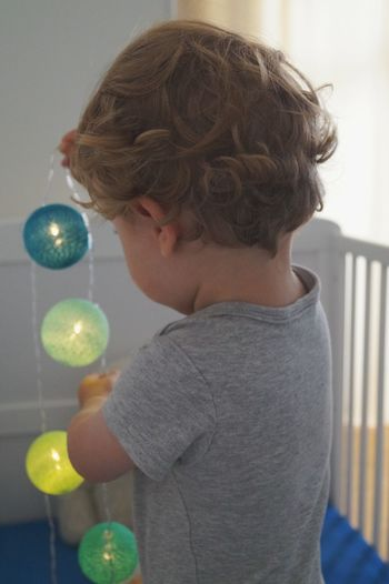 Side view of baby boy holding lighting equipment while standing in crib at home