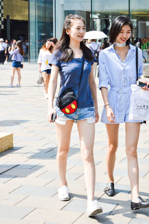 Building Exterior Casual Clothing Day Full Length Happiness Lifestyles Outdoors Real People Smiling Standing Sunlight Walking Young Adult Young Women
