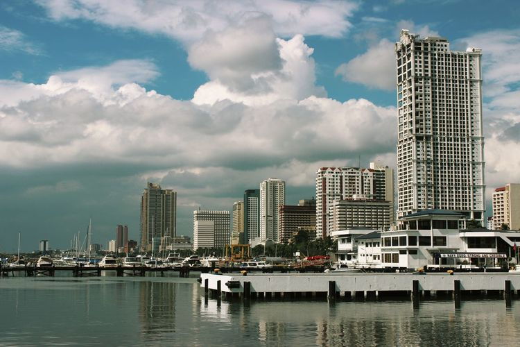 View of harbor with boats and buildings against cloudy sky