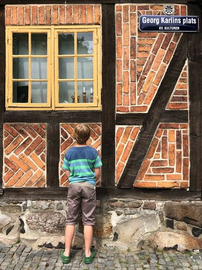 Rear view of boy standing against brick wall