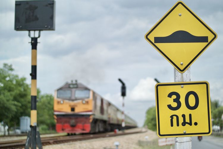 Close-up of speed bump sign by train on railroad track against sky