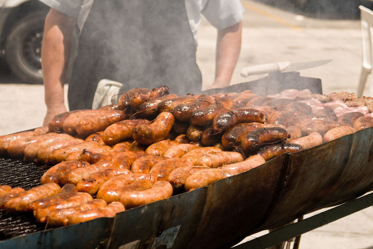 Midsection of man cooking chorizos on barbecue in city
