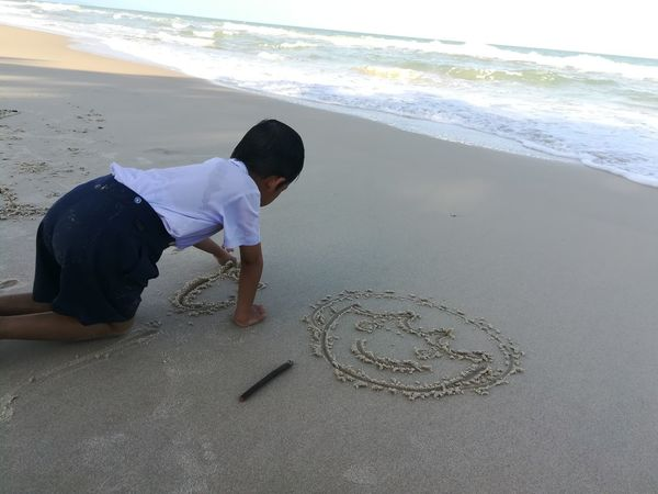 Boy Boy Playing Write On Sand Sea Water Beach Full Length Sand Wave Sky Horizon Over Water