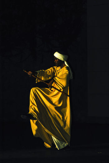 Rear view of person sitting against black background