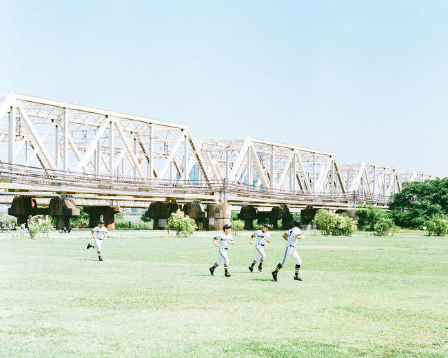 People playing soccer on field against clear sky