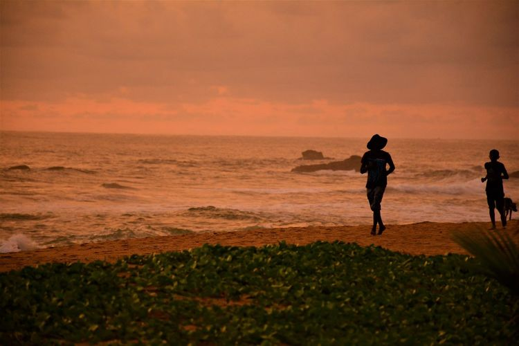Silhouette woman running at beach during sunset