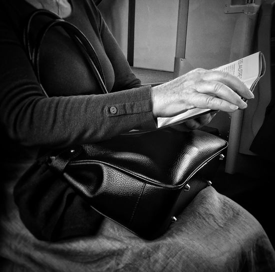 Midsection Of Woman With Handbag Reading Magazine