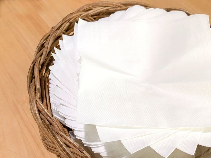 Napkin paper sheets are arranged in a spiral in the basket on the wooden desktop. EyeEm Selects White Color No People Textile High Angle View Pattern Day Indoors  Basket Creativity Art And Craft Directly Above Container Close-up Wood - Material Table
