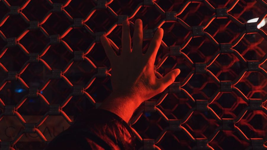 Cropped hand of man touching fence with illuminated red light at night
