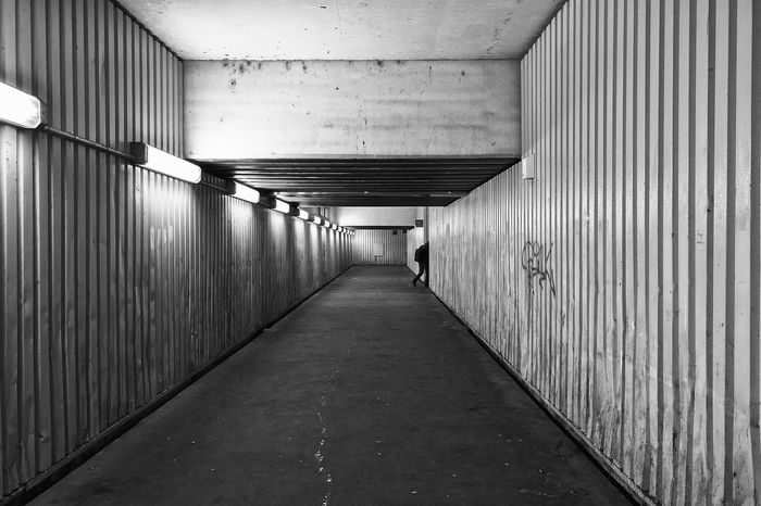 Hurry up. Architecture Blackandwhite Built Structure Dark Day Desolate Fluorescent Bulb Graffiti Illuminated Indoors  Leading Lines One Person Squalid Subway The Way Forward Underpass Vanishing Point Nusshain 12 16 The Architect - 2017 EyeEm Awards