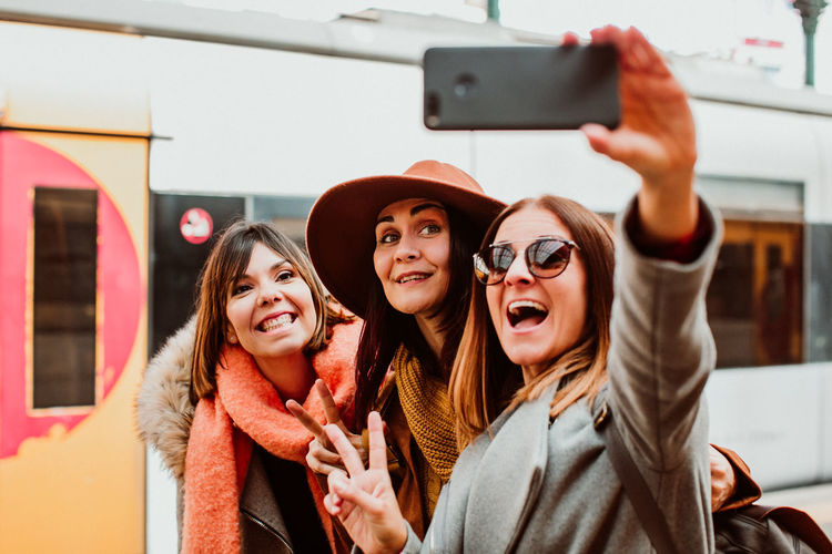 Happy friends taking selfie while standing on station