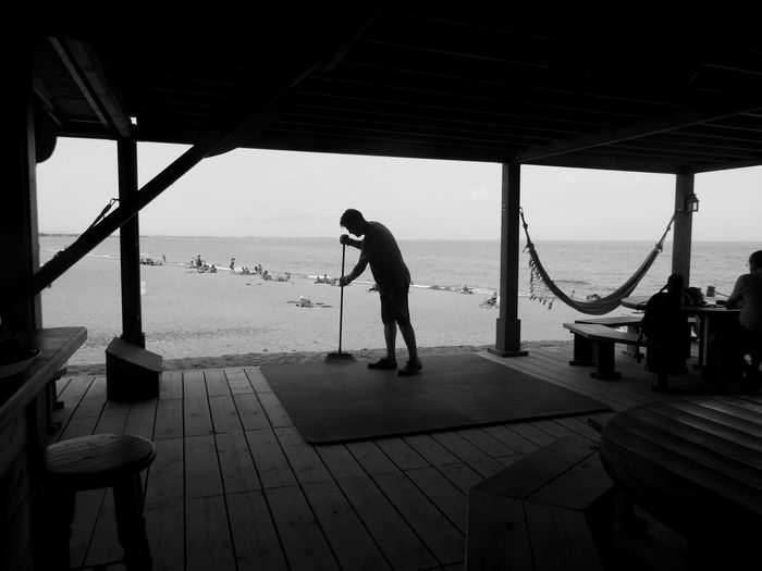 Man cleaning cafe at beach
