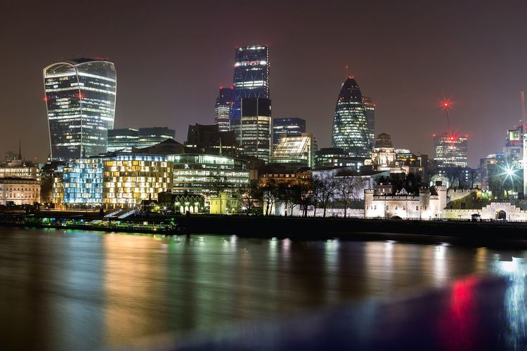 Thames river by illuminated cityscape at night
