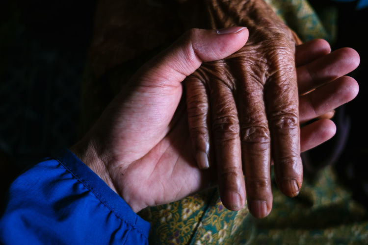 Cropped image of man holding woman hand