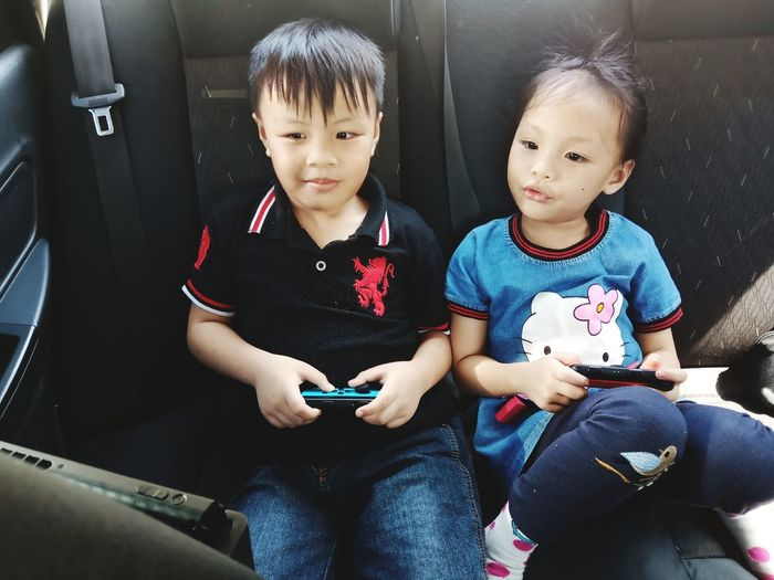 High angle view of siblings sitting on mobile phone
