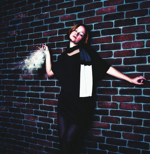 Beautiful woman holding liquor bottle against brick wall