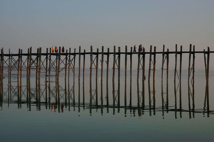 People walking on footbridge with reflection in sea against sky