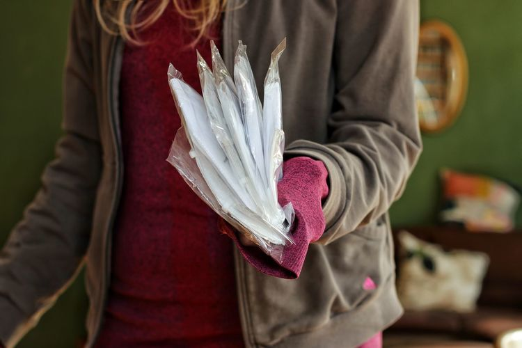Midsection of woman holding paper while standing at home
