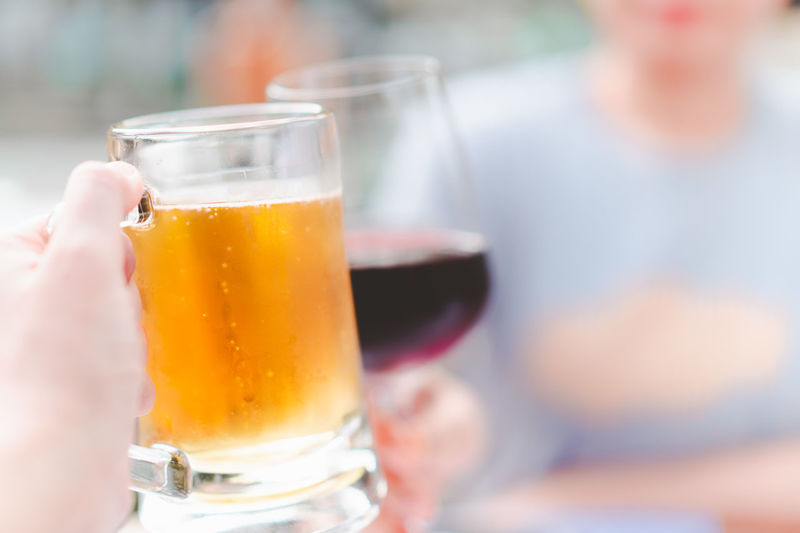 hand holding beer mug smash with wine glass at restaurant, selective focus Alcohol Bar Beer Beverage Bright Celebrate Cheers Chill Cold Day Difference  Dinner Drink Focus Fresh Friends Glass Golden Hand Happy Hold Mug Party People Red Refreshment Relax Restaurant Selective Yellow