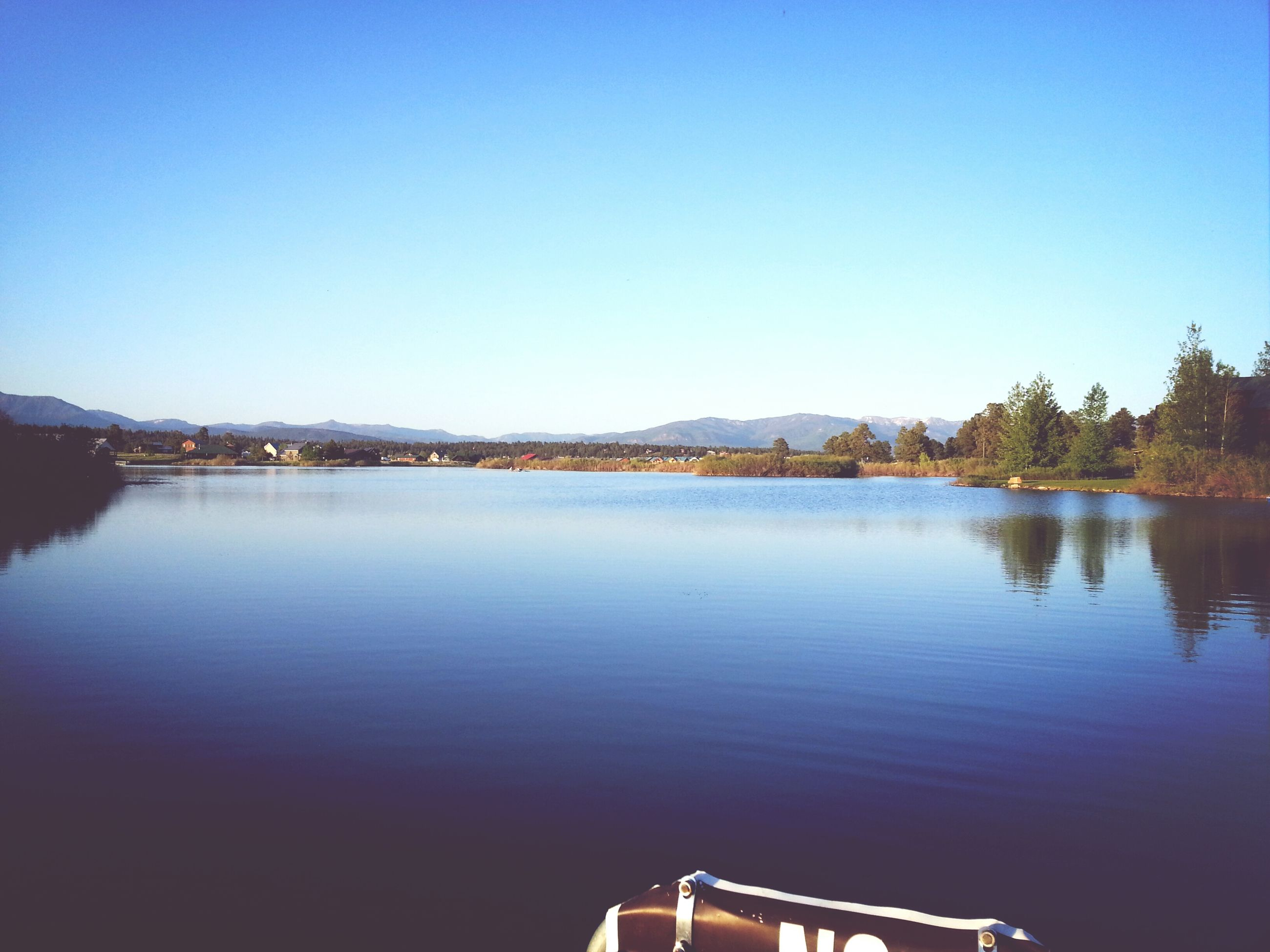 clear sky, copy space, water, blue, built structure, lake, reflection, architecture, waterfront, river, tranquil scene, tranquility, building exterior, scenics, nature, beauty in nature, outdoors, no people, day, mountain