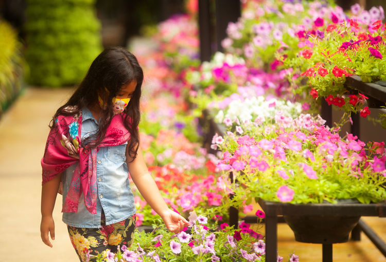 Girl wearing mask looking at flowers in greenhouse