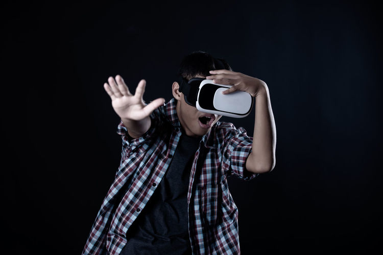 Portrait of a boy holding camera over black background