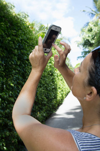 Woman taking a photo with smart phone Day Focus On Foreground Leisure Activity Lifestyles Outdoors Path Pathway Photographing Smart Phone Weekend Activities Woman