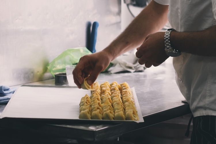Cropped Image Of Man Preparing Dumplings At Kitchen Counter