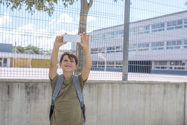 Teenage boy taking selfie while standing against school